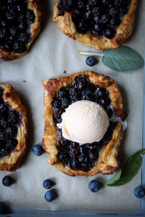 Mini blueberry tarts with scoop of vanilla ice cream.