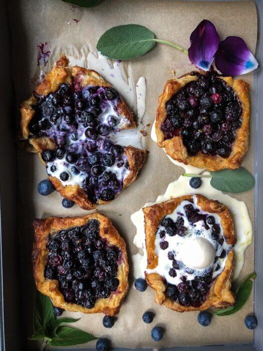 Four blueberry tarts with vanilla ice cream.
