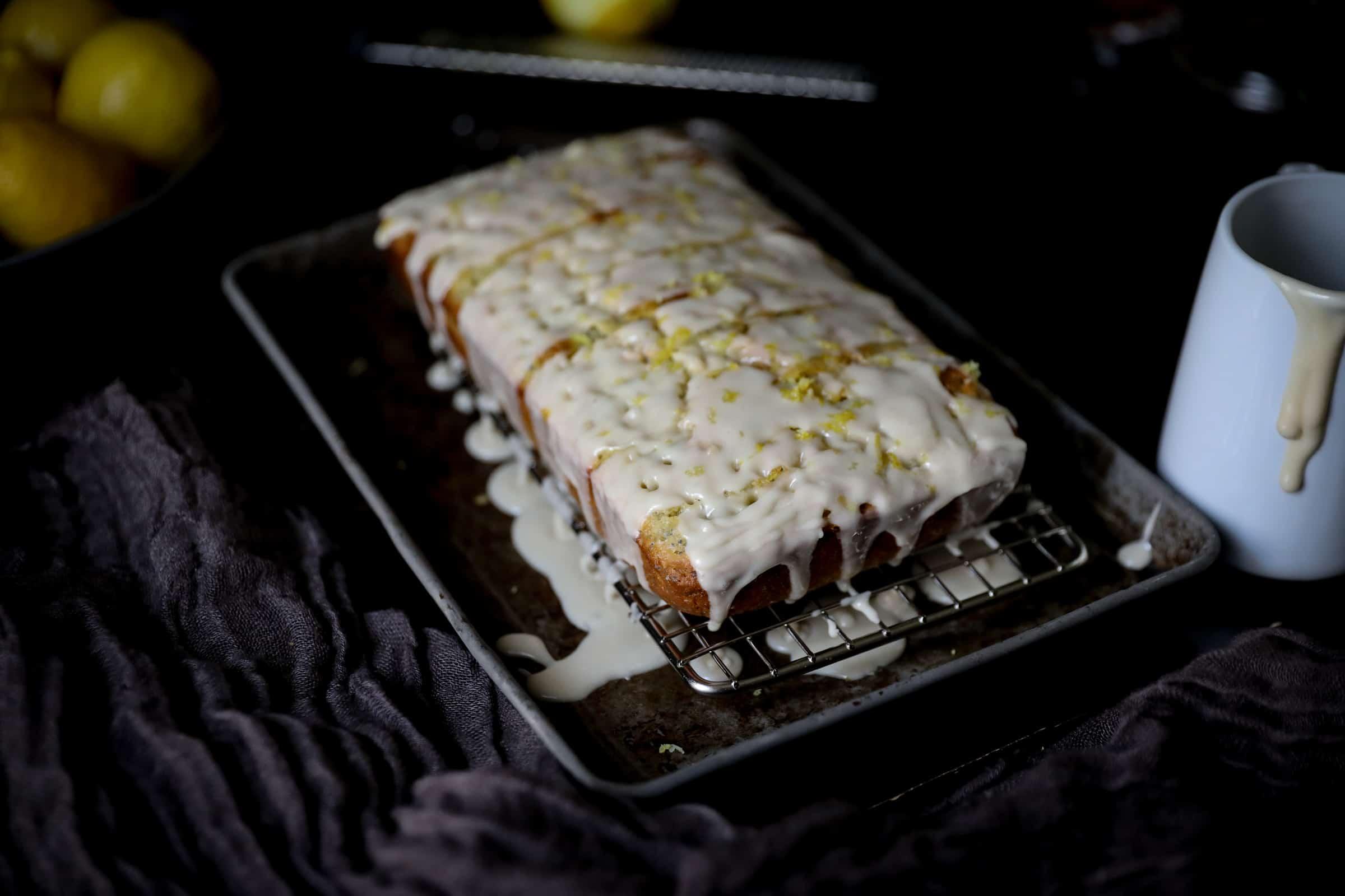 Glazed lemon poppy seed loaf on cooling rack